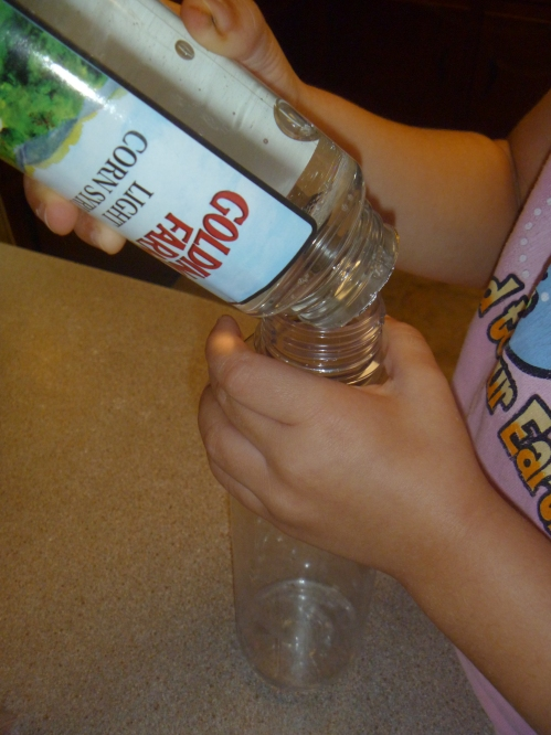 Pour Karo syrup into empty water bottle.